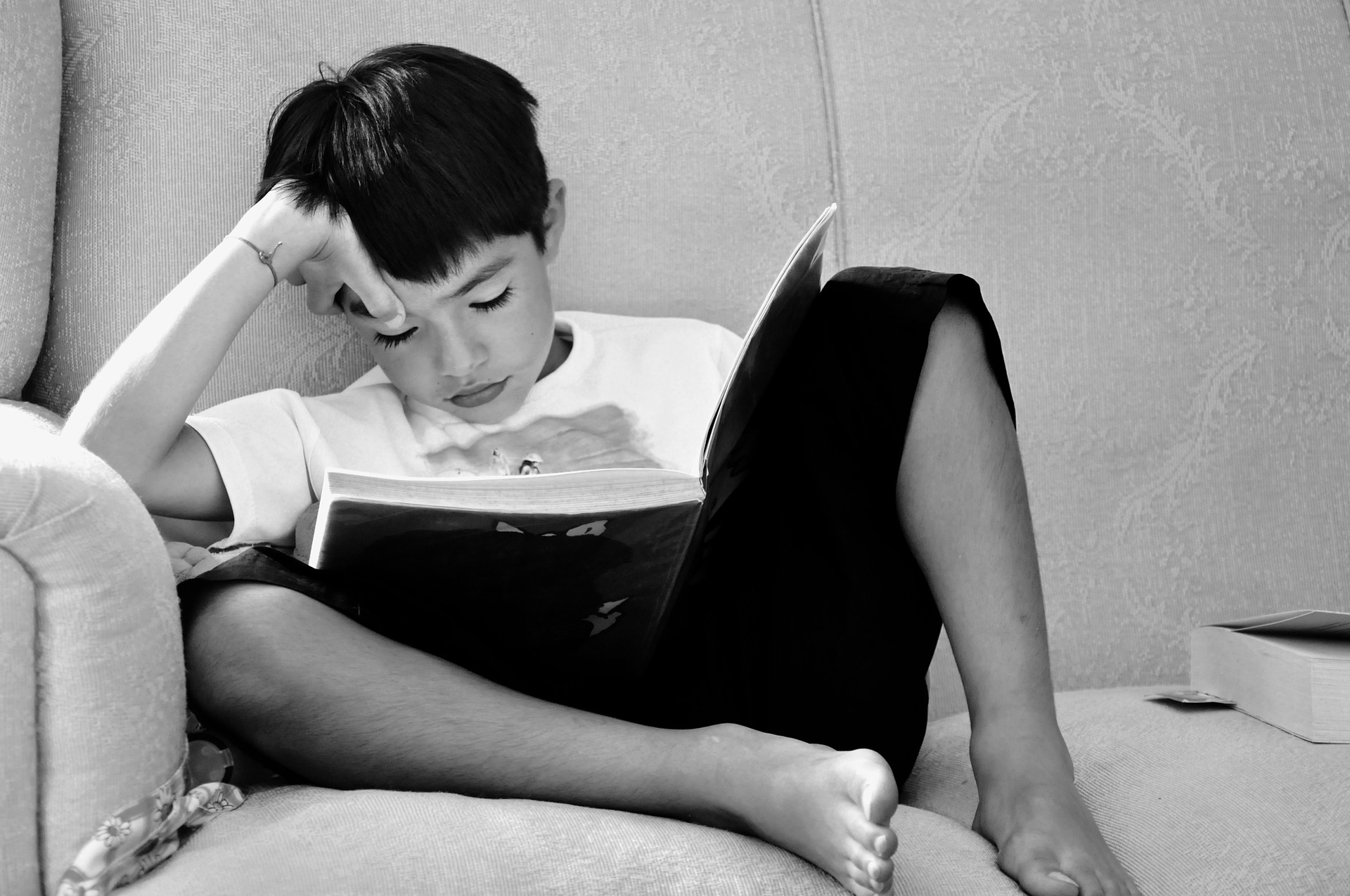 Young boy on a couch, reading a book